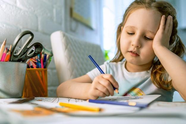 Menina bonitinha pinta imagens com lápis de cor. criança desenha livro para colorir.