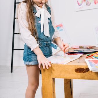 Menina bonitinha pintura com aquarelle na folha de papel na mesa