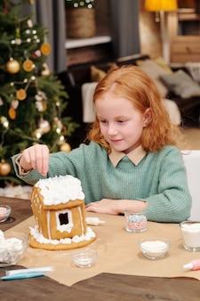 Menina bonitinha polvilhando o telhado de uma casa de pão de gengibre decorada com creme chantilly enquanto prepara a sobremesa festiva para a festa de natal