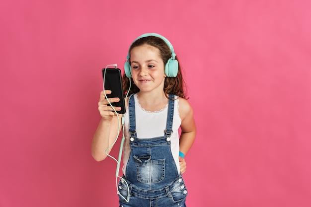 Menina bonitinha posando com um telefone e fones de ouvido em uma parede rosa