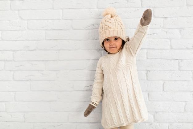 Menina bonitinha posando na frente de uma parede
