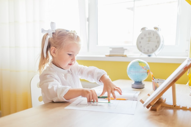 Menina bonitinha pré-escolar com dois ponytales na camisa branca, desenho em casa à mesa. volta ao conceito de escola.