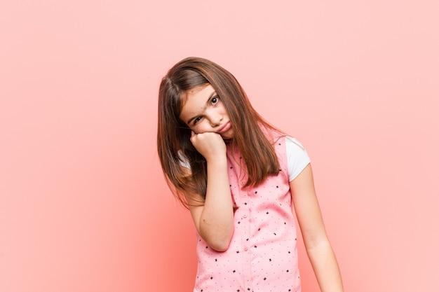 Menina bonitinha que se sente triste e pensativa, olhando para a cópia.