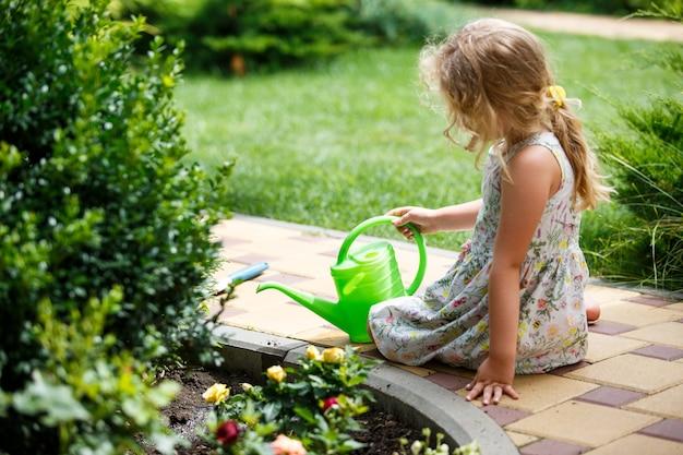 Menina bonitinha regando as plantas no jardim.