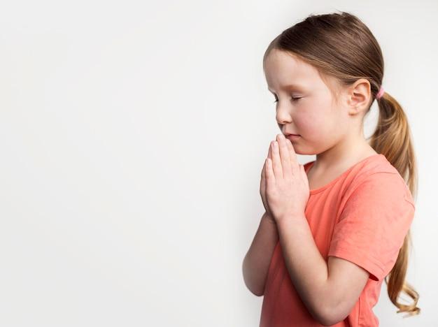 Menina bonitinha rezando com espaço de cópia