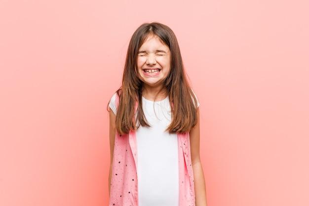 Menina bonitinha ri e fecha os olhos, sente-se relaxada e feliz.