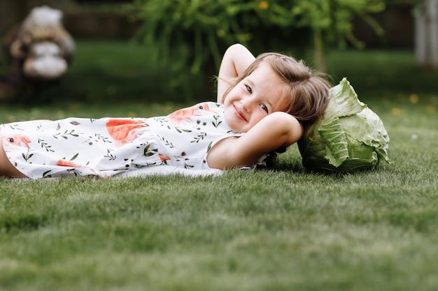 Menina bonitinha rindo e deitada na grama com o repolho