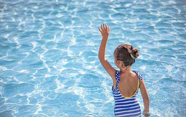 Menina bonitinha se banha em uma piscina de águas claras.