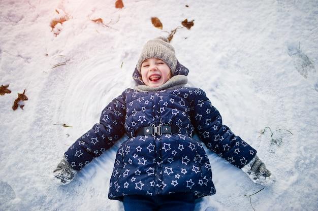 Menina bonitinha se divertindo ao ar livre em dia de inverno.