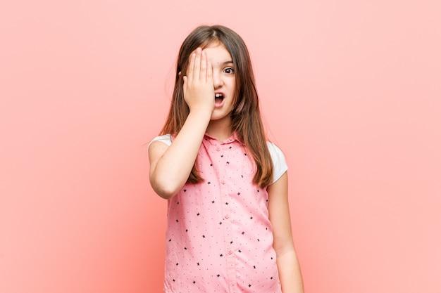 Menina bonitinha se divertindo cobrindo metade do rosto com palm.