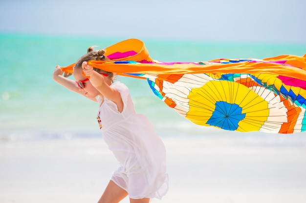 Menina bonitinha se divertindo correndo com pareo na praia tropical