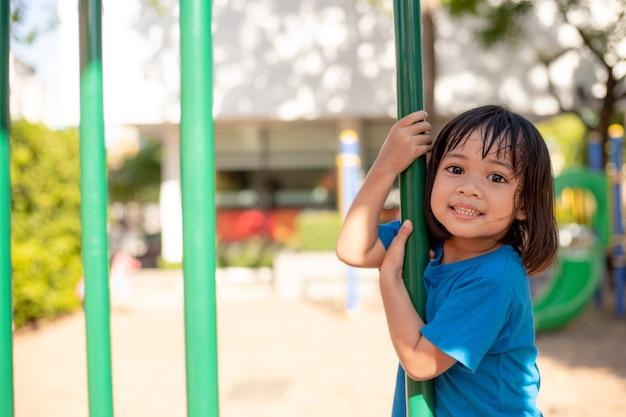 Menina bonitinha se divertindo em um playground ao ar livre no verão
