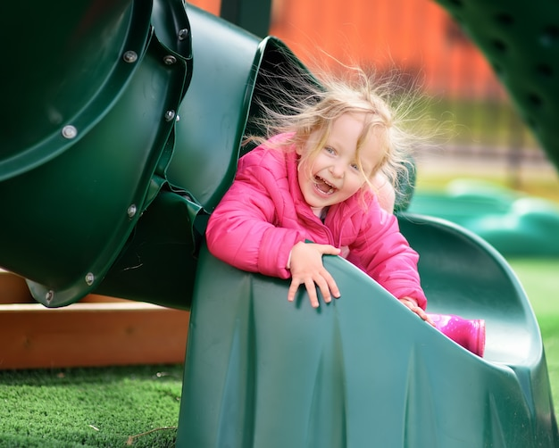 Menina bonitinha se divertindo no playground ao ar livre