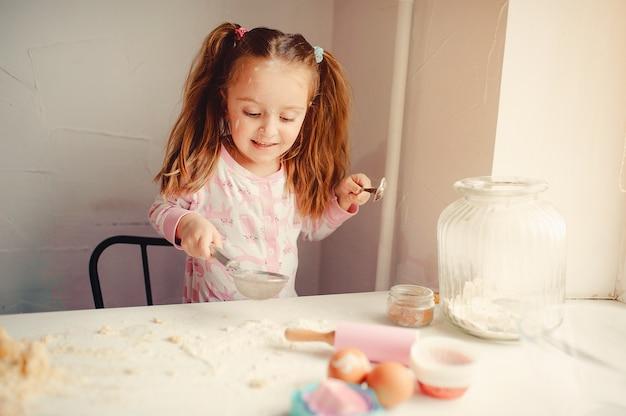 Menina bonitinha se divertir em uma cozinha