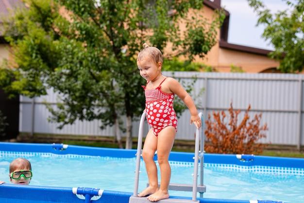 Menina bonitinha se preparando para pular na água azul, se divertindo na piscina, piscina fina em casa, horário de verão na creche, conceito de férias e férias.