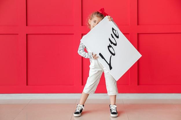 Menina bonitinha segurando a foto com a palavra amor na cor. celebração do dia dos namorados