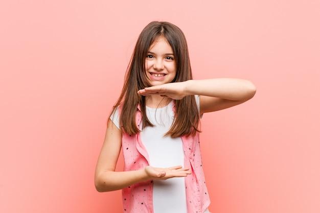 Menina bonitinha segurando algo com as duas mãos, apresentação do produto
