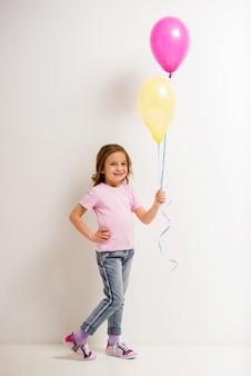 Menina bonitinha segurando balões rosa e amarelos.