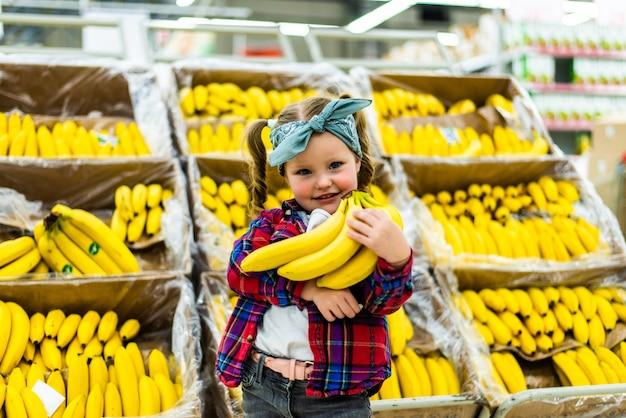 Menina bonitinha segurando bananas em uma mercearia ou supermercado