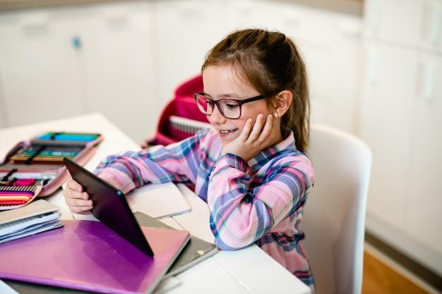 Menina bonitinha segurando o tablet enquanto fazia sua lição de casa. educação online