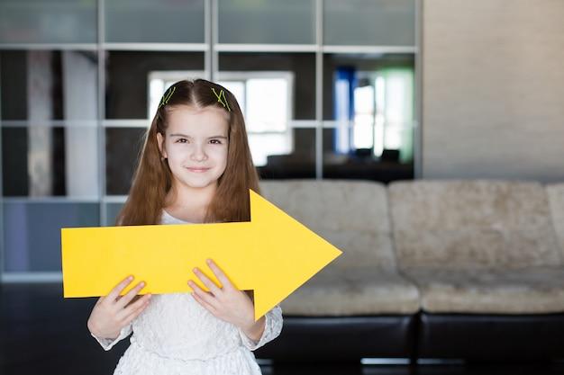 Menina bonitinha segurando um cartaz amarelo em branco na forma de uma seta mostrando direita
