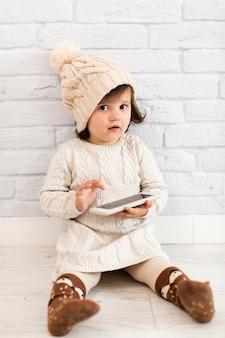Menina bonitinha segurando um telefone