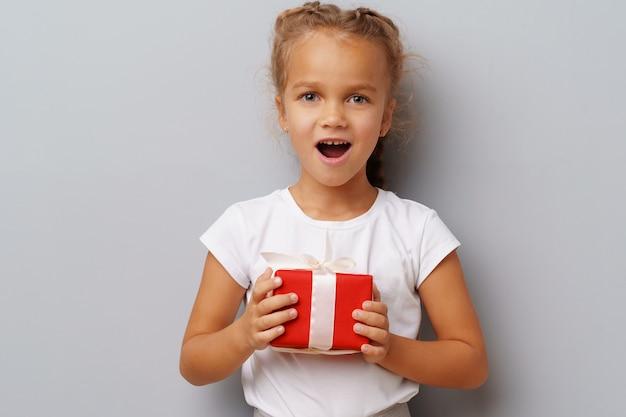 Menina bonitinha segurando uma caixa de presente vermelha nas mãos