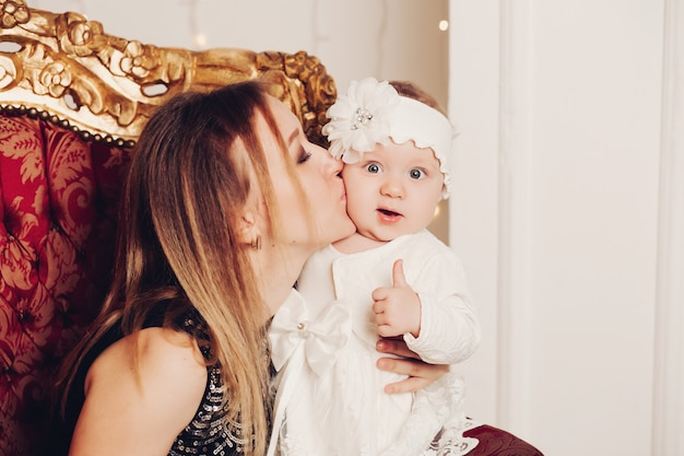 Menina bonitinha sentada com a mãe. época de natal.
