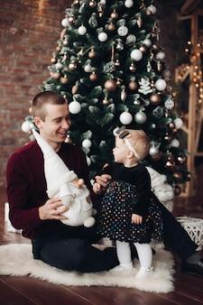 Menina bonitinha sentada com seu pai com árvore de natal