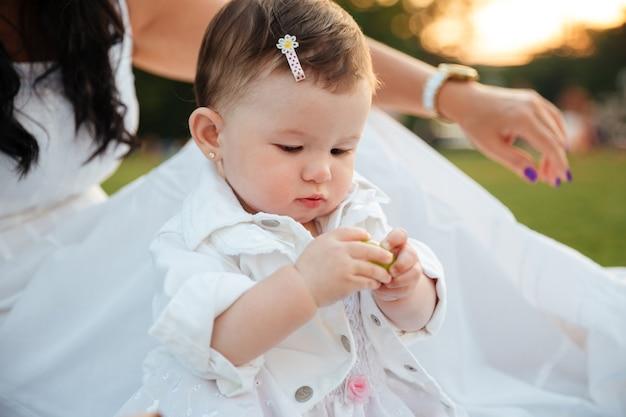Menina bonitinha sentada e brincando ao ar livre