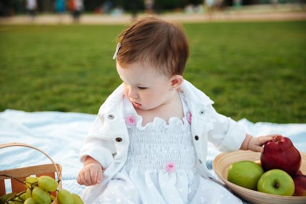 Menina bonitinha sentada e escolhendo frutas no piquenique