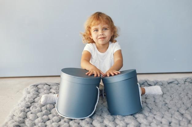 Menina bonitinha sentada em um estúdio com caixa de presentes