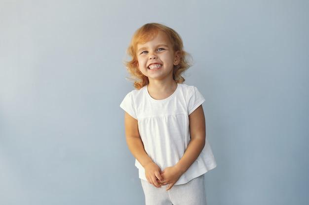 Menina bonitinha sentada em um estúdio em um fundo azul