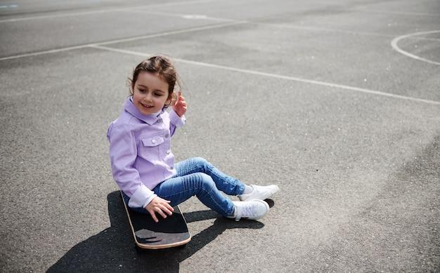 Menina bonitinha sentada em um skate em um playground de esportes em um lindo dia de sol