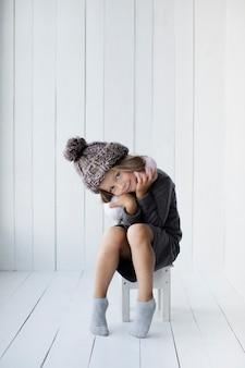 Menina bonitinha sentada em uma cadeira
