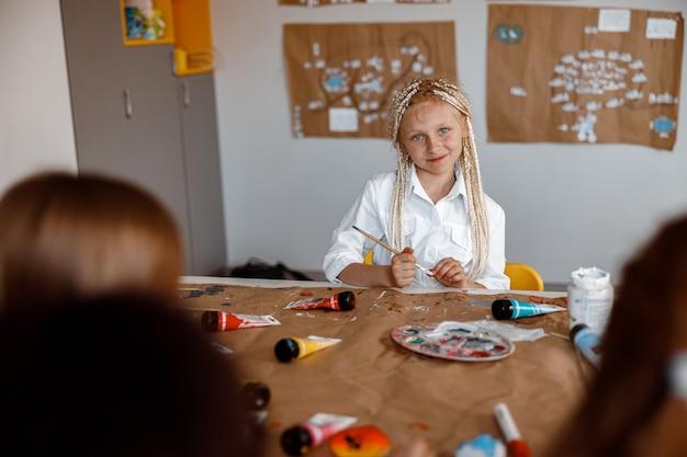 Menina bonitinha sentada em uma mesa em uma aula de desenho