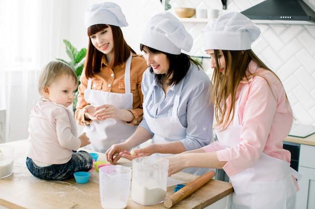 Menina bonitinha sentada na mesa e sua linda mãe, tia e avó de avental estão preparando massa para bolos e sorrindo enquanto cozinhava na cozinha em casa. conceito de dia das mães