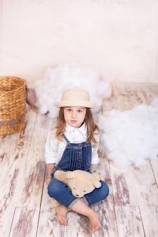 Menina bonitinha sentada no chão e segurar um ursinho de pelúcia. menina brinca na sala de crianças com um brinquedo.