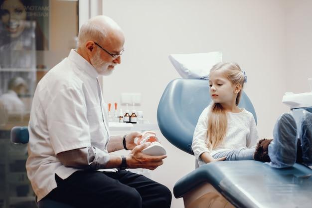 Menina bonitinha sentada no consultório do dentista
