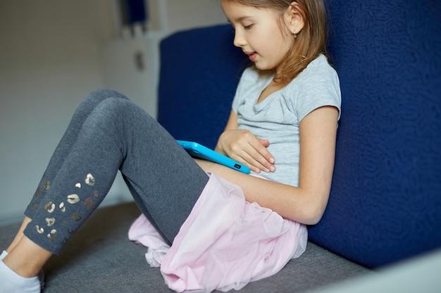 Menina bonitinha sentada no sofá, criança viciada em tecnologia, curtindo um jogo online no computador tablet digital, usando aplicativos, informações de navegação na web em casa,