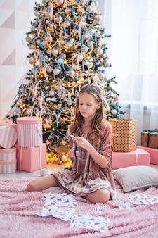 Menina bonitinha sentada perto da árvore e fazendo flocos de neve de papel