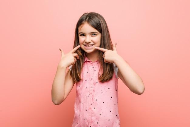 Menina bonitinha sorri, apontando os dedos na boca.