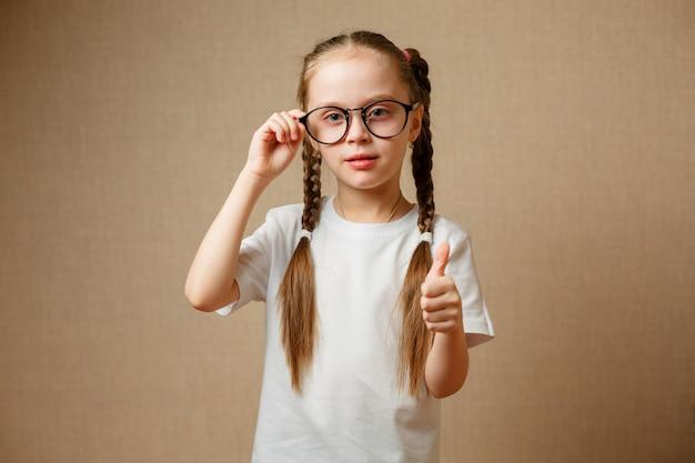 Menina bonitinha sorridente com óculos pretos, mostrando os polegares