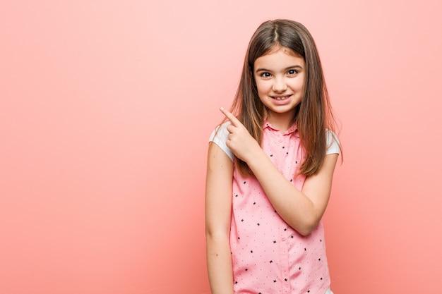 Menina bonitinha sorrindo e apontando de lado, mostrando algo no espaço em branco.