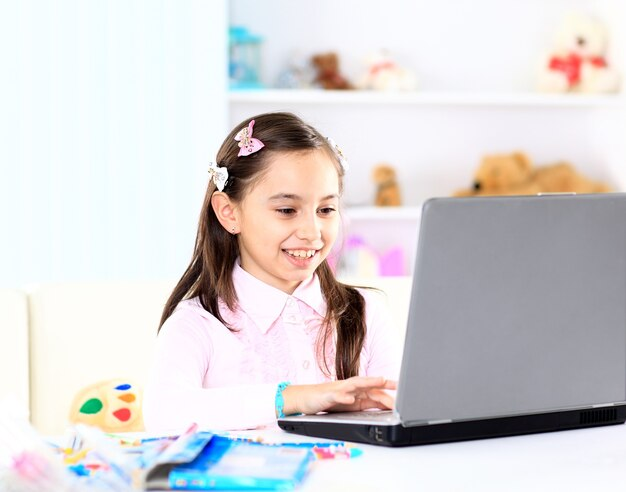 Menina bonitinha sorrindo e olhando para o laptop