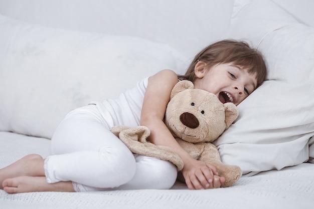 Menina bonitinha sorrindo enquanto estava deitada em uma confortável cama branca