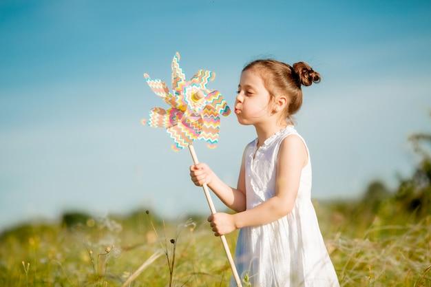 Menina bonitinha sorrindo verão no campo segurando um moinho de vento