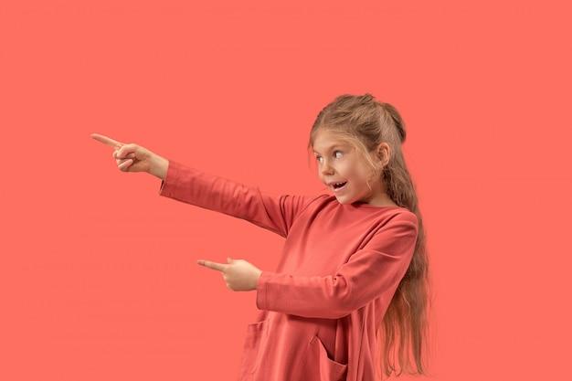 Menina bonitinha surpresa com vestido coral e cabelo comprido sorrindo para a câmera