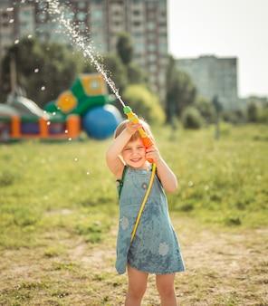 Menina bonitinha tocando pistola de água