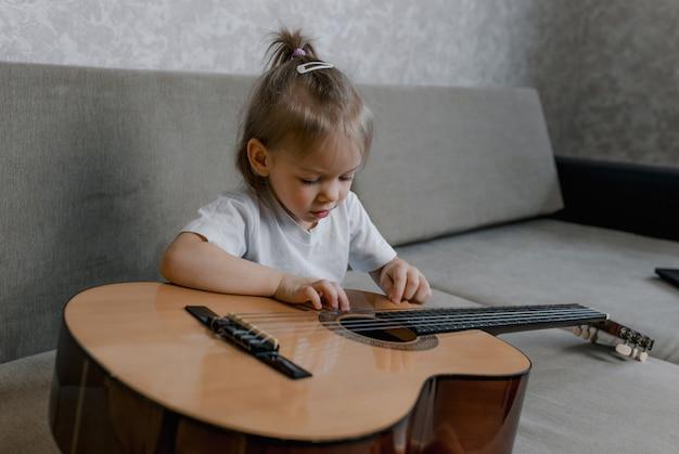 Menina bonitinha tocando violão no sofá da sala. jogos infantis e entretenimento